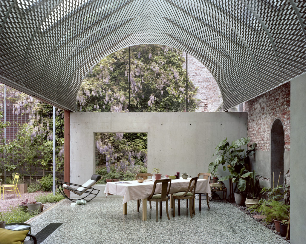 Speckled mint green terrazzo floors lay underneath a fantastic barrel-vaulted metal structure that shades the enclosed deck. The addition is delightfully tactile.
